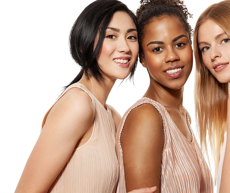 Three women coming together looking at the camera over their shoulders